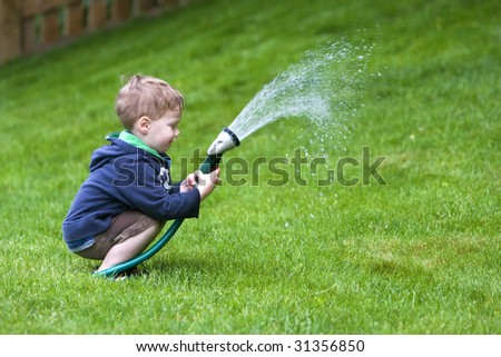 Handsome young boy watering garden with rubber hosepipe