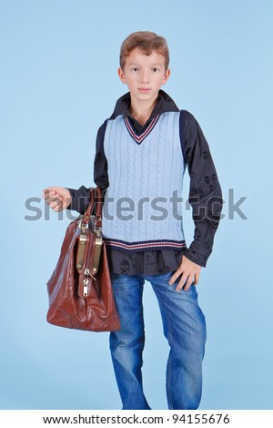Handsome young boy wearing hat and with carpetbag