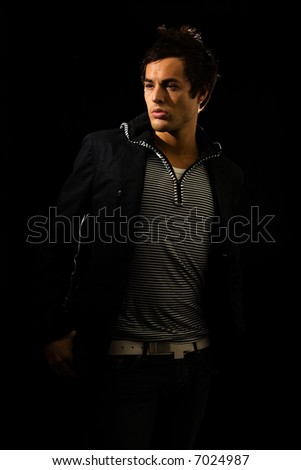 Handsome young brunette man wearing a striped shirt and dark jacket on black in shadow