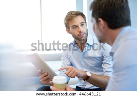Handsome young business entrepreneur holding a digital tablet while talking about ideas with his mature corporate manager