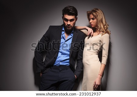 Handsome young business man holding his hands in pockets and looking at the camera while his lover is leaning on him, looking down.