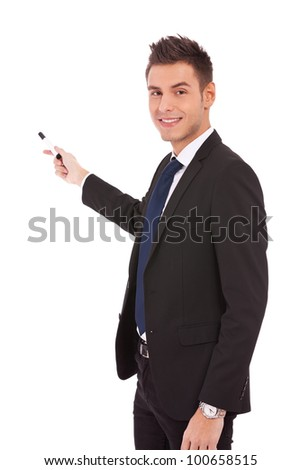 handsome young business man in a suit pointing with a pen on white background - stock photo