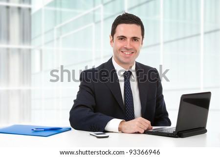 Handsome young business man in blue suit in office with laptop.
