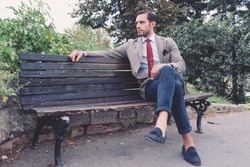 Handsome young  business man in the park after work, vintage style, retro filtered look