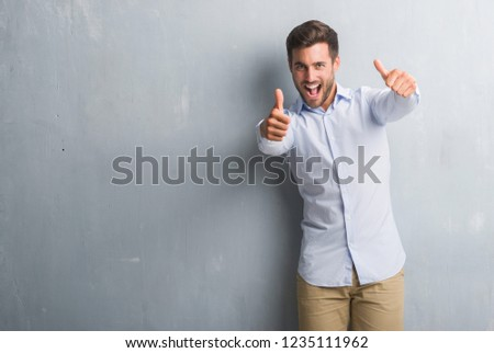 Handsome young business man over grey grunge wall wearing elegant shirt approving doing positive gesture with hand, thumbs up smiling and happy for success. Looking at the camera, winner gesture.