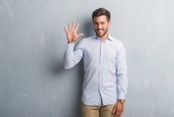 Handsome young business man over grey grunge wall wearing elegant shirt showing and pointing up with fingers number five while smiling confident and happy.