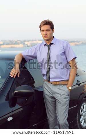 Handsome young business man relaxed near car, outside