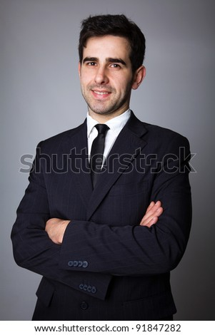 Handsome young business man standing on grey background