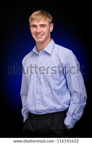 Handsome young business man standing with hands in pocket against dark background