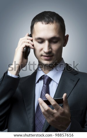 Handsome young business man with a mobile phone and a card - stock photo