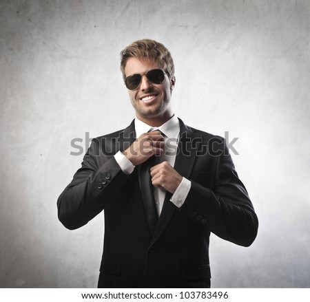 Handsome young businessman adjusting his tie
