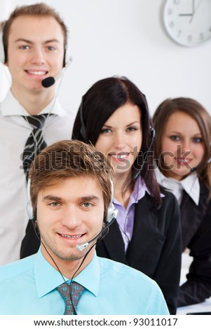 handsome young businessman and colleagues in a call center office, Attractive Smiling  businesspeople in support phone, operators with headset at workplace, agent friendly looking at camera