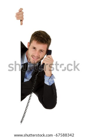 Handsome young businessman behind wall holding telephone receiver. Having a conversation. Copy space. Studio shot. White background.