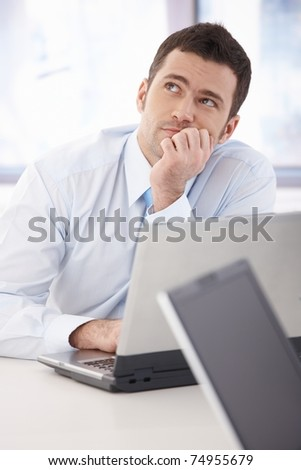 Handsome young businessman daydreaming at desk in office.?
