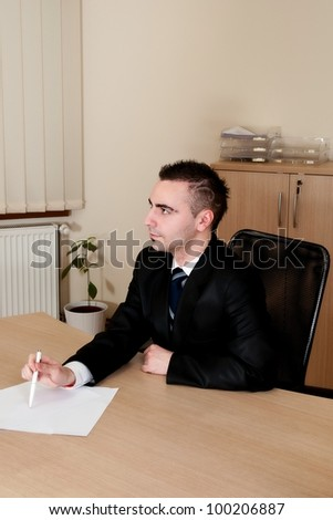 Handsome young businessman in elegant suit working with documents