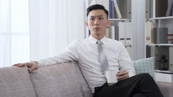 handsome young businessman in formal wear resting on couch with cup of hot tea is in quiet contemplation.