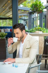 Handsome young businessman in suit drinking coffee in cafe bar