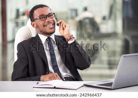 Handsome young businessman is taking a call on a headset as he deals with queries at the customer support call centre.