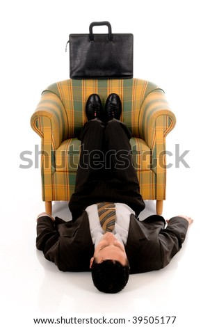 Handsome young businessman meditation yoga position in sofa.  Studio, white background.
