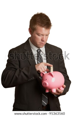 Handsome young businessman saving money in piggy bank isolated