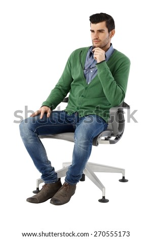 Handsome young businessman sitting and thinking in swivel chair over white background, looking away. Full size. #270555173