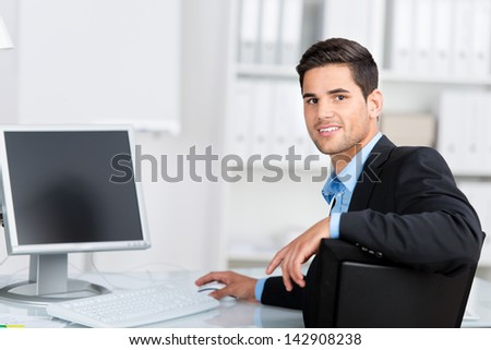 Handsome young businessman sitting at his office in the office working at his computer turning to look at the camera