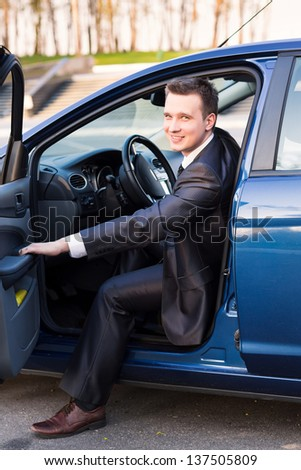Handsome young businessman sitting in his new car