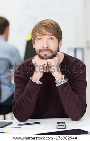 Handsome young businessman sitting thinking at his desk with his chin resting on his hands and eyes raised to heaven