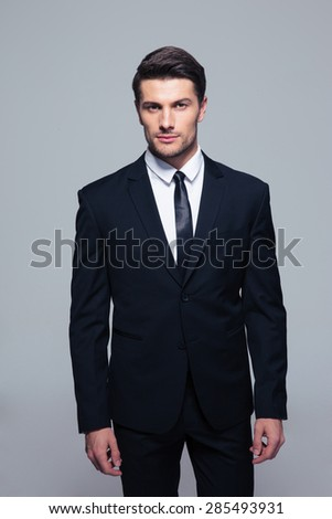 Handsome young businessman standing over gray background and looking at camera
