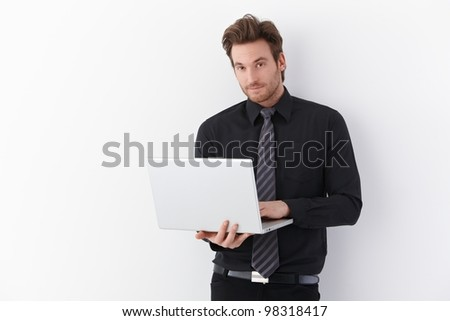 Handsome young businessman standing over white background, holding laptop, smiling.
