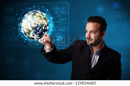 Handsome young businessman touching high-tech 3d earth panel