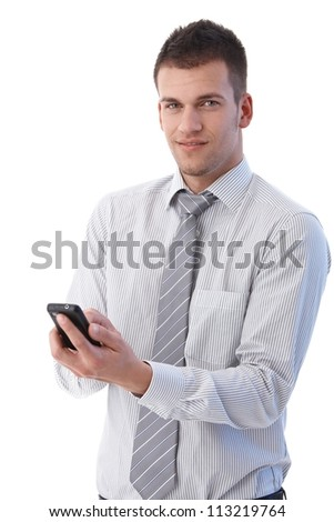 Handsome young businessman using mobile phone, writing text message, smiling.