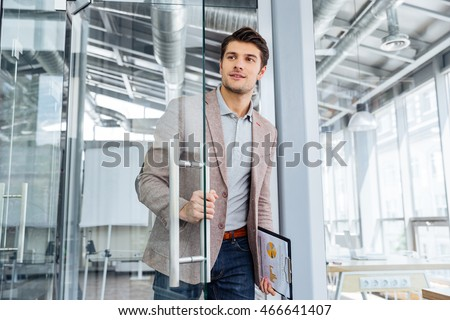 Handsome young businessman with clipboard entering the door in office