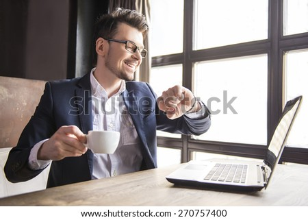 Handsome young businessman working at laptop with cup of coffee in restaurant. And looking at watch.