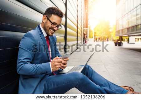 Handsome young businessman working in front of the office
