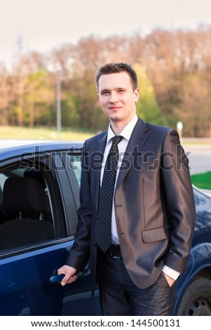 Handsome young businessmanstanding near his new car