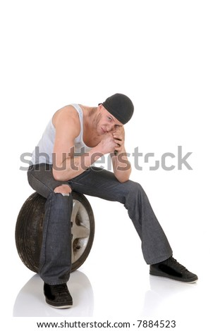 Handsome young car mechanic with wheel, pensive troubled expression on face, white background