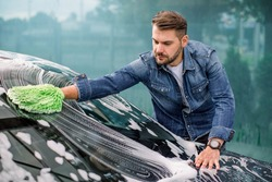 Handsome young Caucasian man cleaning his car windshield with green sponge mitten and soap foam outdoors at car wash service