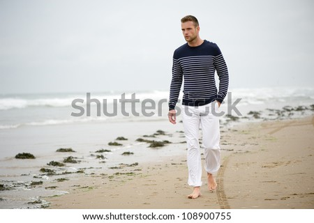 Handsome young Caucasian man walking alone with bare feet on the beach