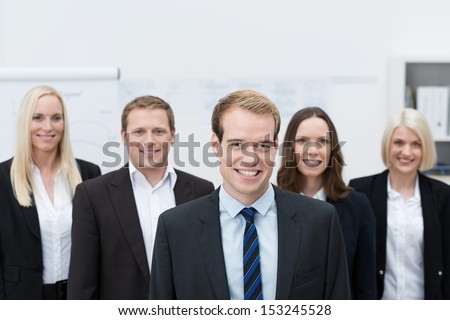 Handsome young Caucasian manager smiling with a happy team made of three women and a man, behind him