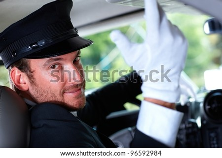 Handsome young chauffeur in elegant car, smiling.?