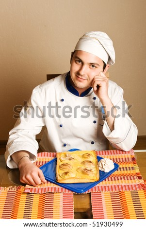 handsome young chef in the professional manner in the living room with cake from pears