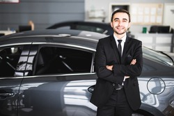 Handsome young classic car salesman standing at the dealership in front of new car