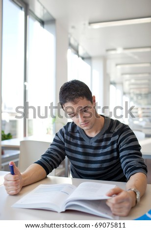handsome young college student in a library (shallow DOF; color toned image)