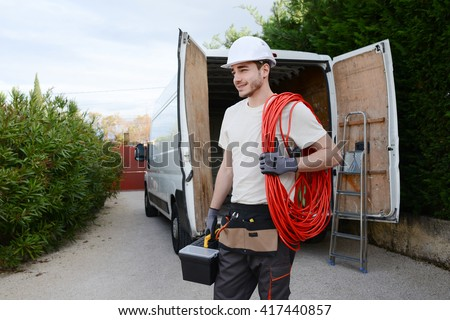 handsome young construction worker with his commercial van on background #417440857