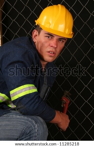 handsome young construction workman with safety helmet and spanner