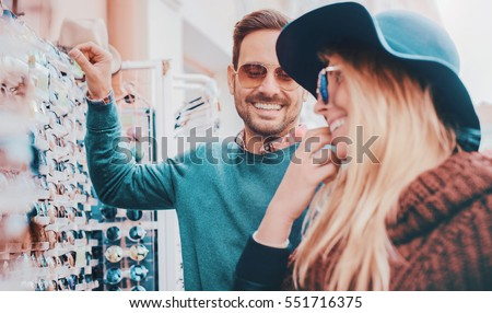 Handsome young couple buying sun glasses at street vendor. Consumerism, shopping, lifestyle concept
