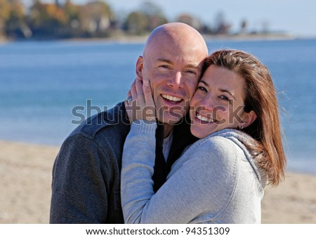 Handsome young couple hugging at the beach in winter