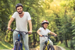 Handsome young dad and his cute little son are looking forward and smiling while riding bikes in park