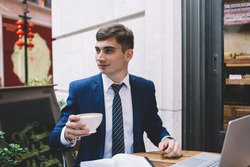 Handsome young entrepreneur wearing elegant blue suit and striped tie looking away and holding cup of coffee while sitting on cafe terrace during lunch break